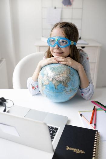 Portrait of cute girl wearing eyeglasses on table