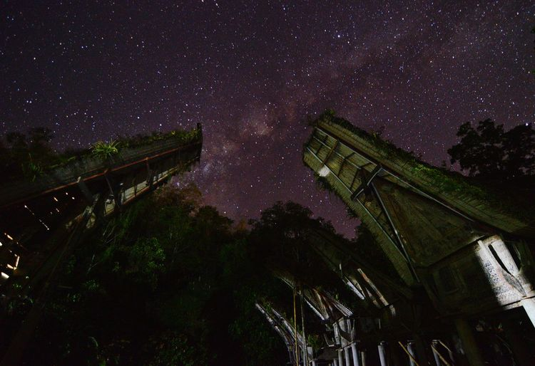Low angle view of built structures against star field at night