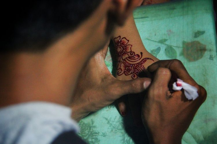 Midsection Of Man Applying Henna Tattoo On Woman Hand