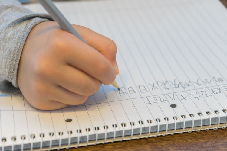 Cropped Hand Of Child Writing In Book