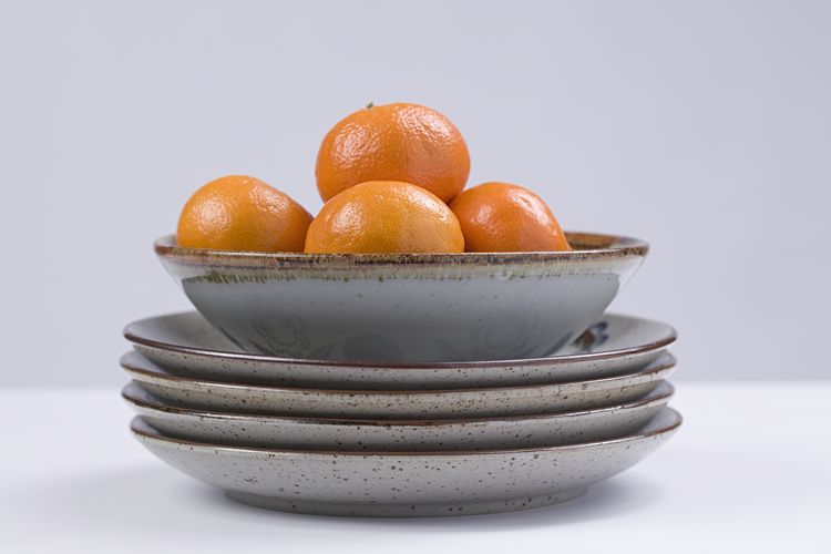 Close-up of oranges in bowl against white background
