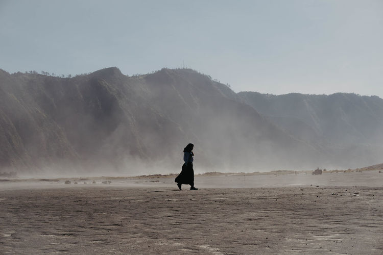 Woman walking on land against mountains and sky