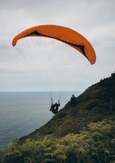 Person paragliding over sea against sky