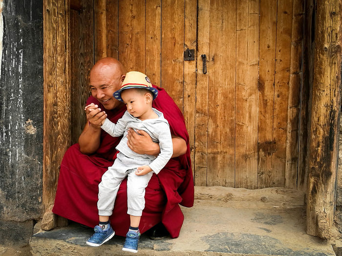 Monk With Boy Crouching By Door