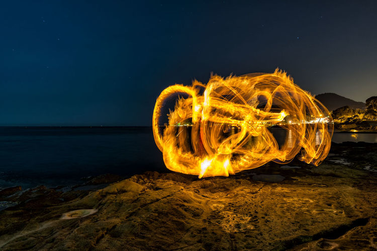 Light painting on beach against sky at night