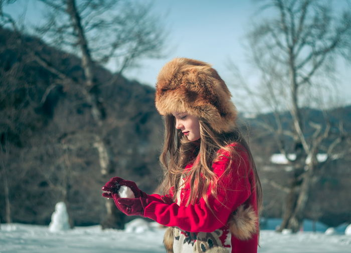 Smiling girl wearing fur hat while holding snow outdoors