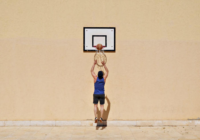 Adult Adults Only Basketball - Sport Basketball Hoop Competition Copy Space Day Exercising Full Length High Wall Joyful Jumping One Person People Reflections Score Sport Stretching Success Victory You Can Make It If You Try Young Adult Live For The Story The Street Photographer - 2017 EyeEm Awards Paint The Town Yellow