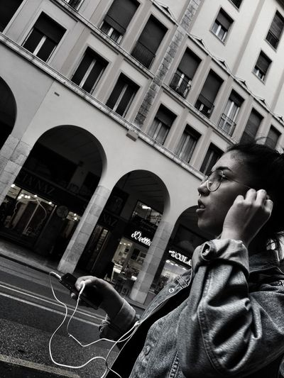 Low Angle View One Person Architecture Lifestyles Built Structure Building Exterior Real People People Adult Women Girl Street Photography Black And White Model Casual Clothing City Life City Street Bianco E Nero Ragazza EyeEm Gallery EyeEm Best Shots Listen To Music Music Listening Music The Street Photographer - 2017 EyeEm Awards Black And White Friday