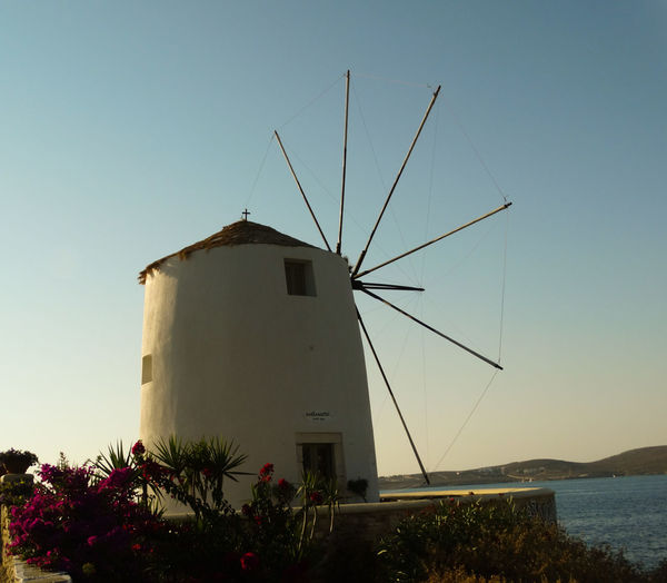 Traditional windmill by sea against clear sky