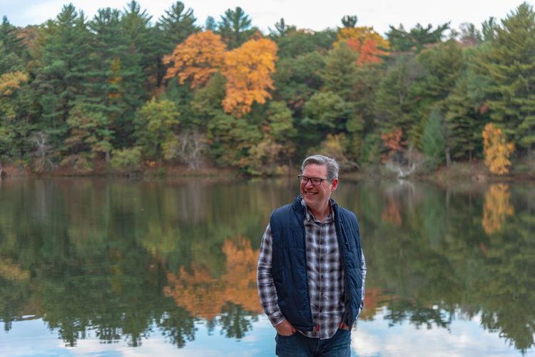 Smiling man standing against lake during autumn