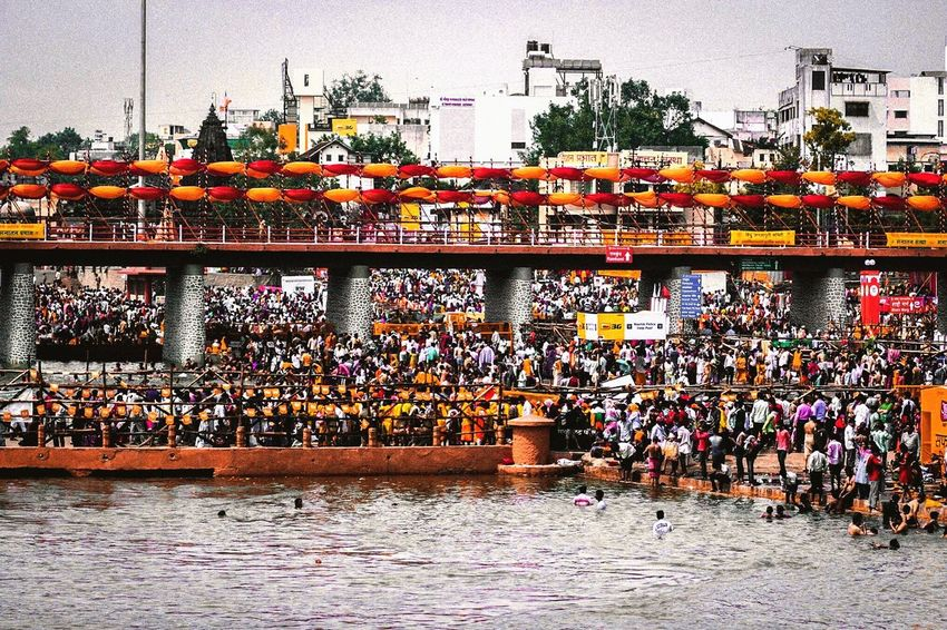 Low angle view of people at kumbh mela 2015 Large Group Of People Real People Outdoors Celebration Built Structure Building Exterior Architecture Day Tree Crowd Sky Competition Water Nature