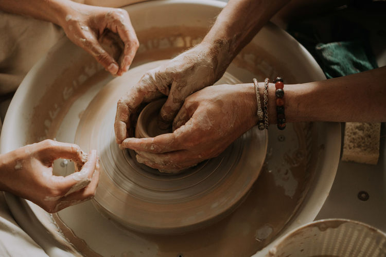 Potter teach teenage girl working with pottery wheel. top view. close up.