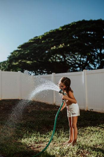 Full length of girl standing in water at yard