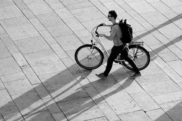 High angle view of man walking with bicycle on footpath