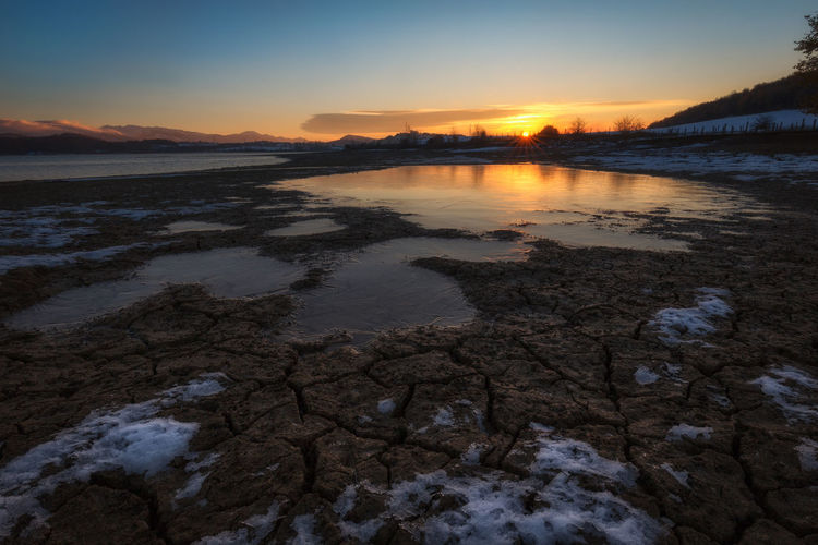 Scenic view of frozen beach against sky during sunset