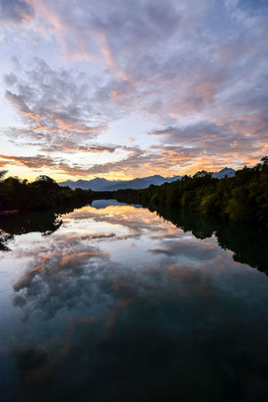 Clouds and sunset sky reflecting in wide mirror like still river with tree lined banks and mountain range horizon. Beauty In Nature Clouds Colorful Sky Idyllic Lake Landscape Mirror Reflection Mountain Mountain Range Outdoors Peace Reflection Remote Scenics Sky Reflection Still River Sun Down Sunset Tranquility Travel Tree Lined Tree Lined Bank Water Reflections
