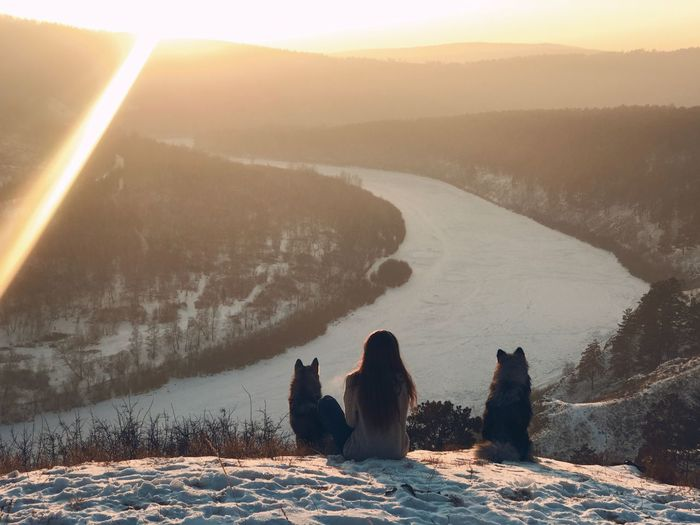Woman with dogs sitting on mountain during sunset