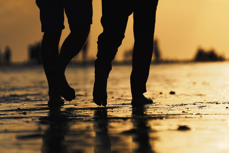 Low section of silhouette people on beach