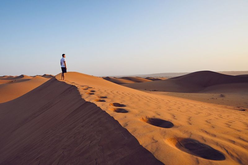 Young man standing on top of sand dune and looking at view. Desert Wahiba Sands in Oman. Sand Dune Desert Wahiba Sands Oman Travel Men Travel Destinations One Person Scenics - Nature Beauty In Nature Real People Arid Climate Nature Sand Adventure Exploring Journey Freedom FootPrint Walking Hiking Lonely Contemplation Inspiration Calm