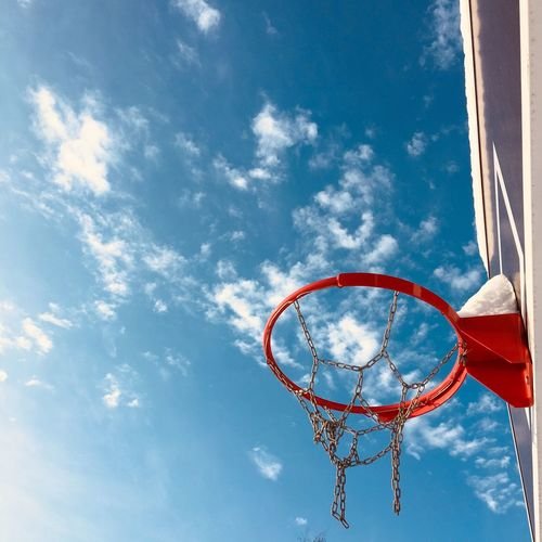 Low angle view of basketball hoop against blue sky during sunny day