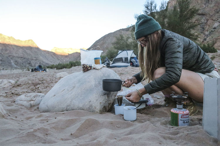 Female hiker brewing a cup of coffee at dawn Adventure Beauty In Nature Coffee Exploration Explore Hike Hiker Hiking Leisure Activity Mountain Mountain Range Nature Nature One Person Outdoor Outdoor Photography Outdoors Rugged Sand Scenics Summer Tent Wild Wilderness Camp