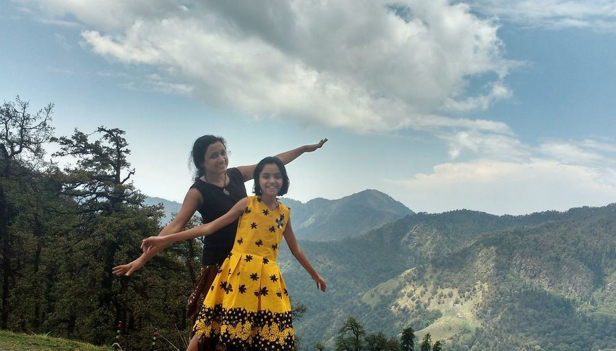 Portrait Of Daughter And Mother With Arms Outstretched Standing On Mountain Against Sky