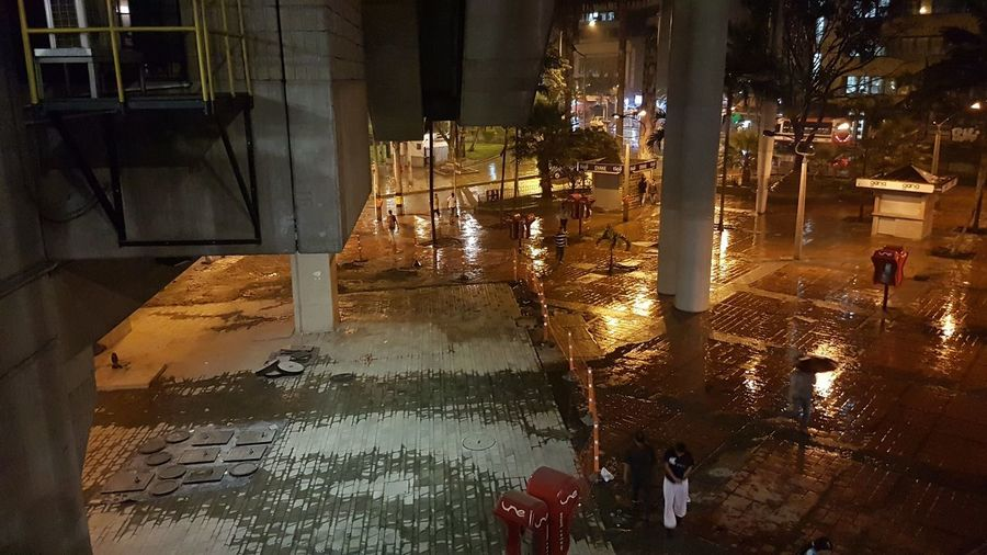 High angle view of wet street amidst buildings in city at night