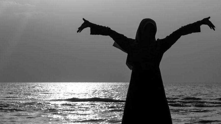 Rear View Of Silhouette Woman With Arms Outstretched Standing By Sea Against Sky During Sunset