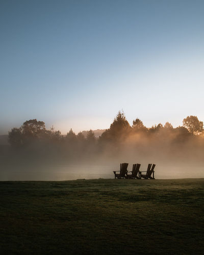 Silhouette chairs on land against clear sky during sunset