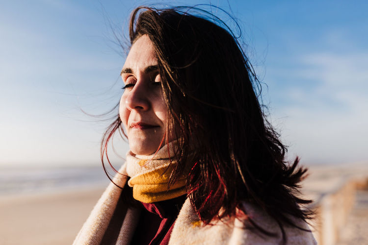 Portrait of woman at beach against sky