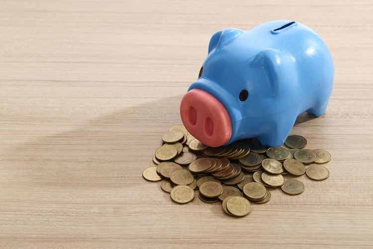 Close-up of blue piggy bank with coins on wooden table
