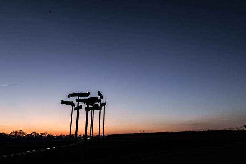 Silhouette cranes against clear sky at sunset
