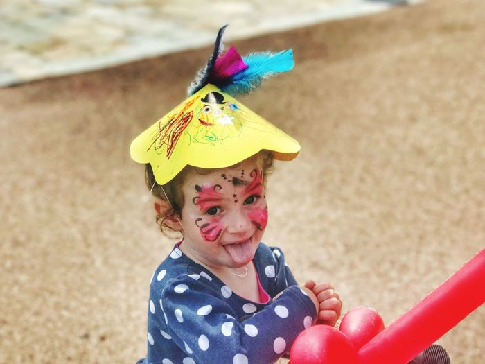 High angle view of girl with face paint and party hat on sand