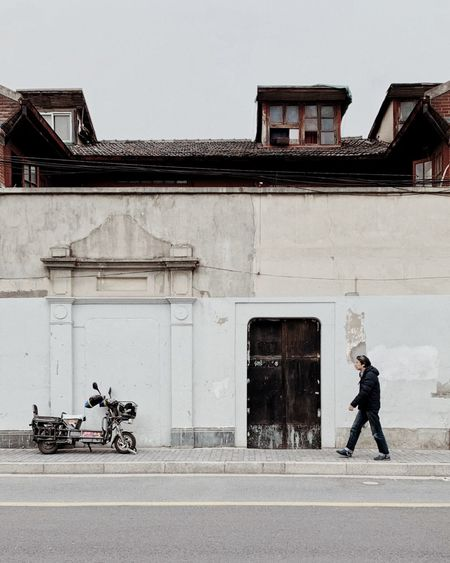 Man walking on street against building in city