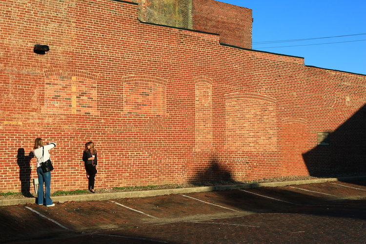 Wide angle of two girls taking pictures against brick wall