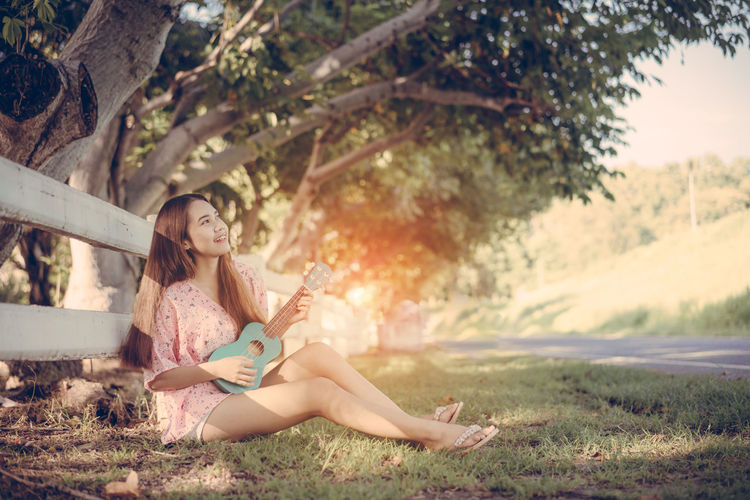 Full length of woman playing ukulele while sitting on grass