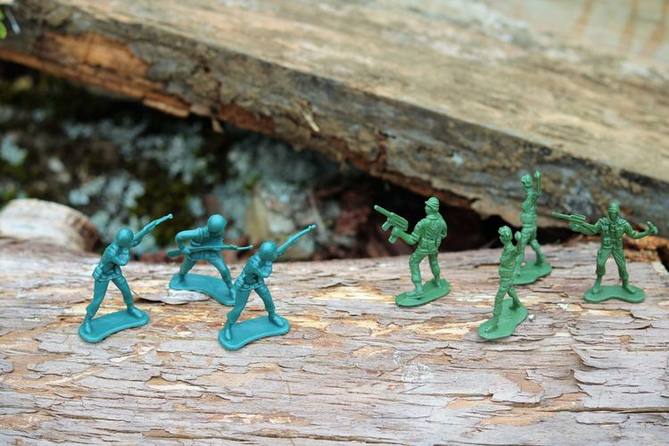 Plastic War Toy Soldiers Uniform Adult Concept Battle Child's Play Childhood Memories Close-up Concept Creativity Day Fighting Figurine  Focus On Foreground Green Color Guns No People Outdoors Plastic Toys Playing Representation Selective Focus Soldiers Fighting Turquoise Colored War Wood - Material
