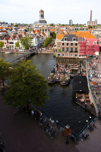 High angle view of people in canal amidst buildings in town