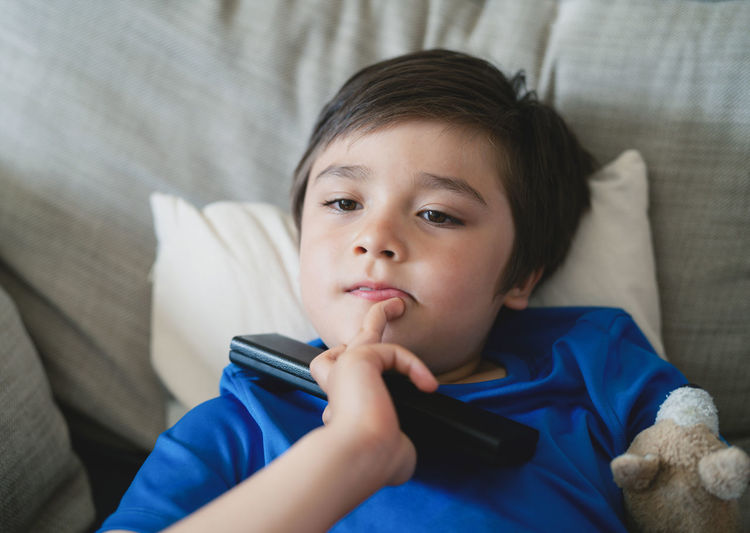 Portrait of boy lying on bed at home