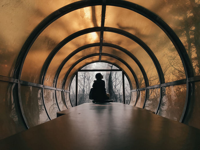 Woman Sitting In Illuminated Tunnel