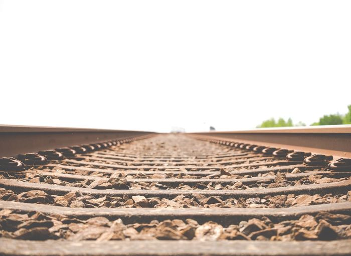 Surface level of rusty railroad tracks against clear sky