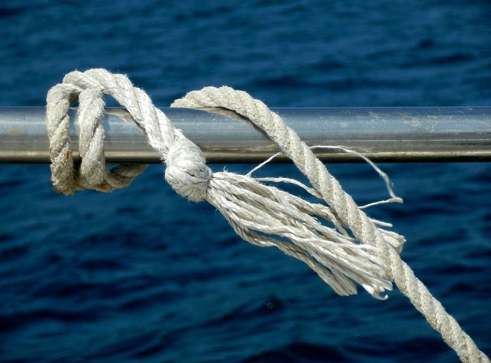 Close-Up Of Rope Tied To Boat Railing Against Sea