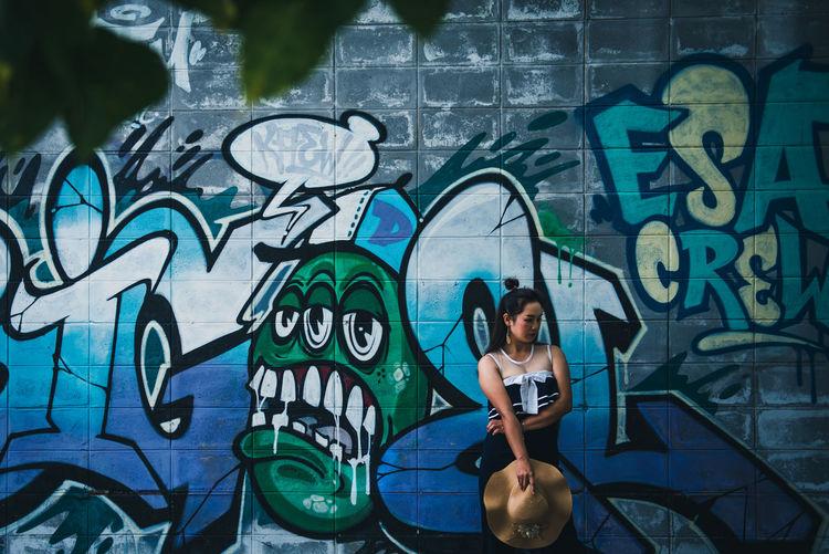 Full length of man holding mobile phone against graffiti wall