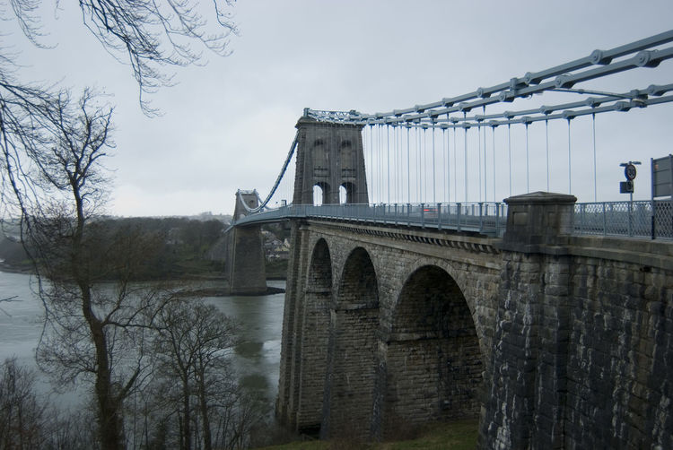 historic suspension bridge across the menai straight between mainland and anglesey, north wales Anglesey Arches Bridge Bridge - Man Made Structure Crossing Diminishing Perspective Engineering Grey Links Metal North Wales Suspeneded Suspension Suspension Bridge Thomas Telford Wales