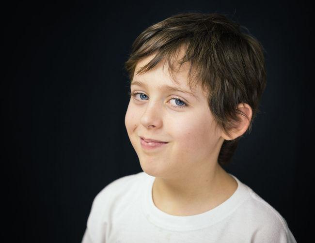 Portrait of smiling boy against black background