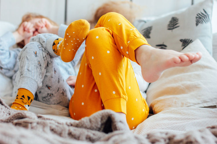 Midsection of child sleeping on bed at home