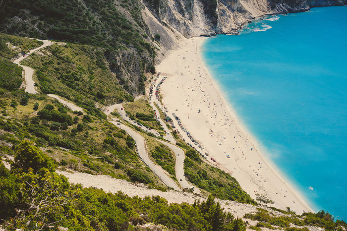 Serpentine road to famous Myrtos Beach with many tourists, Kefalonia, Greece Beach Beauty In Nature Blue Day Environment High Angle View Idyllic Land Landscape Mountain Myrtos Beach Nature No People Non-urban Scene Outdoors Paradise Plant Scenics - Nature Sea Serpantine Tourism Tranquil Scene Tranquility Water Zigzag
