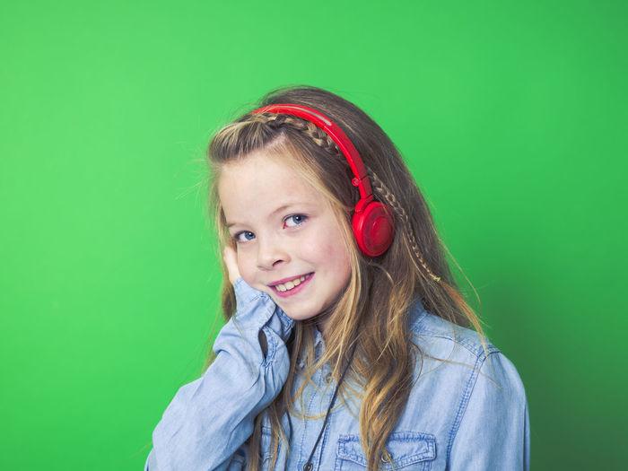 Portrait Of Smiling Girl Listening Music Through Headphones Against Green Background