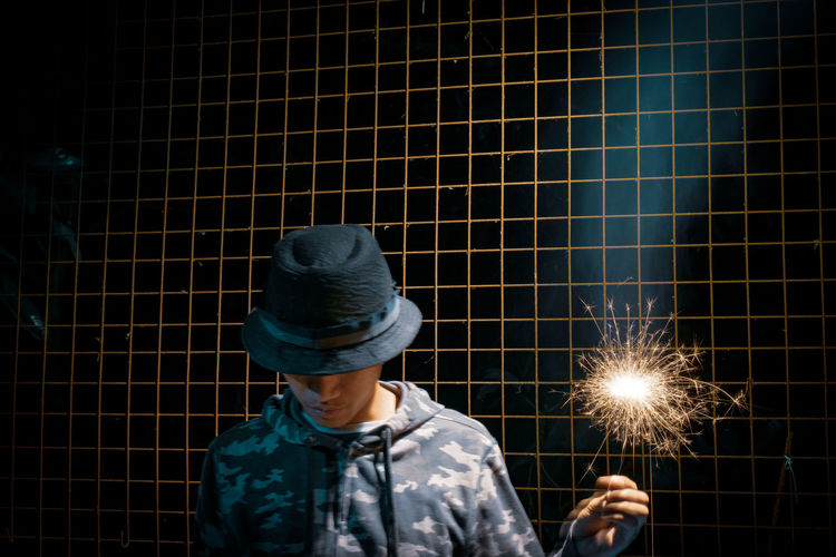Man wearing hat holding illuminated sparkler against fence