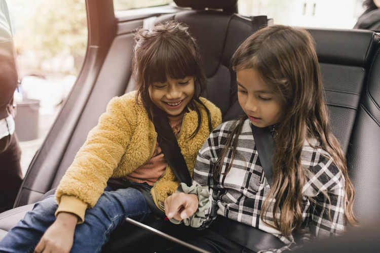 Girl and woman sitting in car